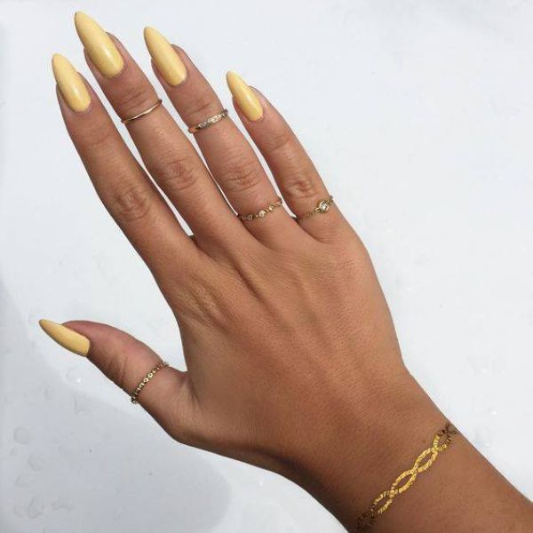 Yellow color nail polish on nail extensions