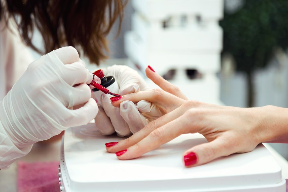 Pink nail polish being applied onto the nails