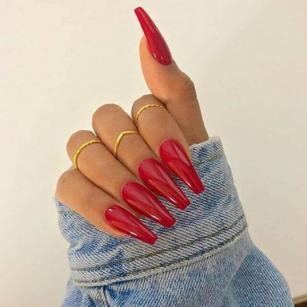 Red color nail polish on long nail extensions